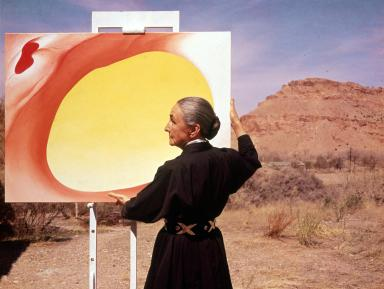 American artist Georgia O'Keeffe (1887 - 1986) stands at an easel outdoors, adjusting a canvas from her 'Pelvis Series- Red With Yellow,' Albuquerque, New Mexico, 1960. (Photo by Tony Vaccaro/Getty Images)